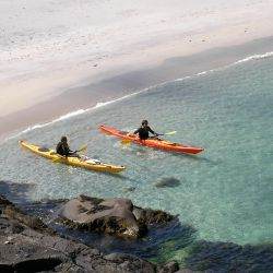 sea kayakers leaving the beach