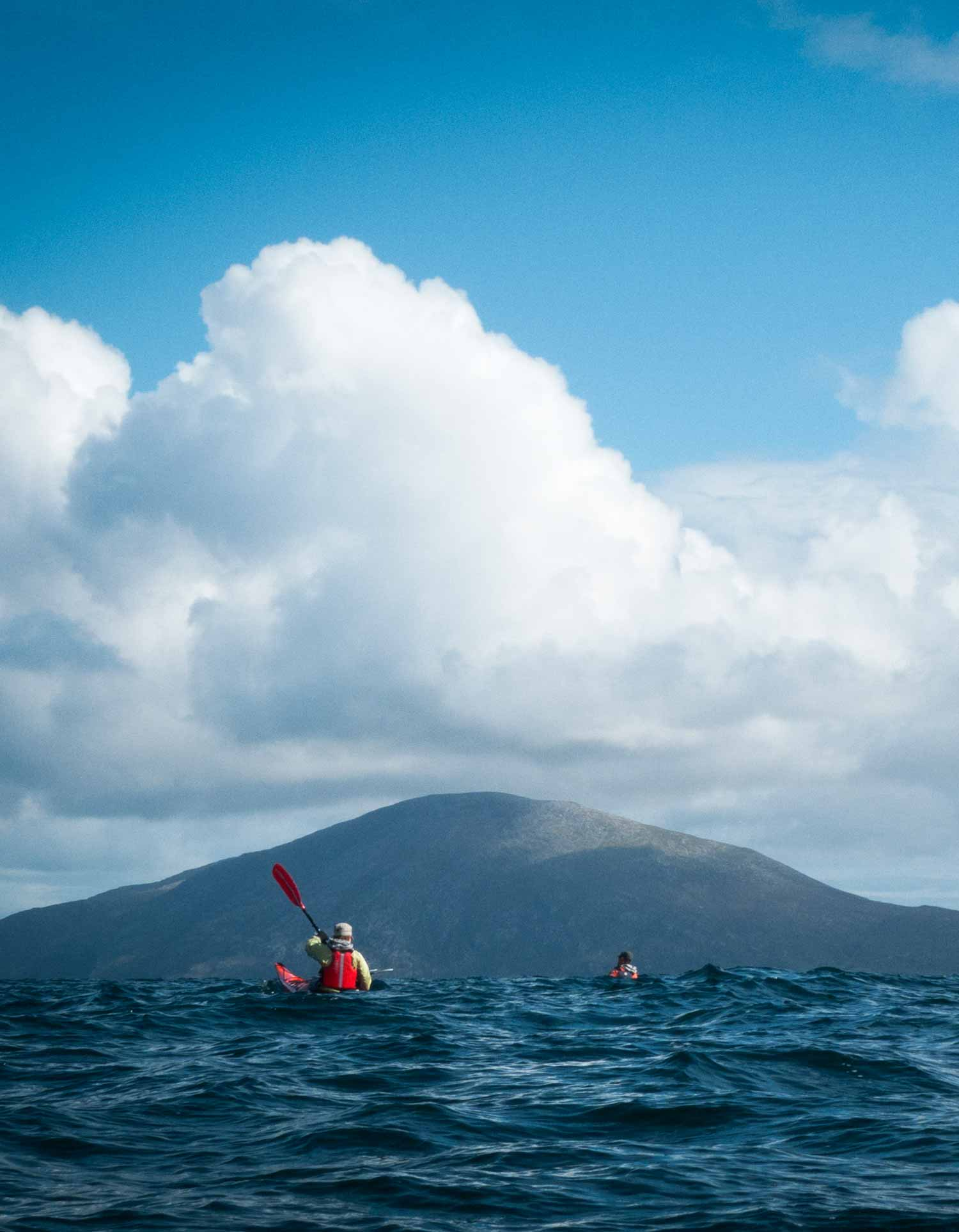 sea kayaks in ocean swells with mountains of Harris