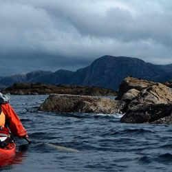 kayaking past rocks with mountains in the distance