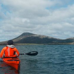 paddler enjoying sea loch with mountain view