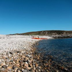 pebbly beach with kayaks on Uist